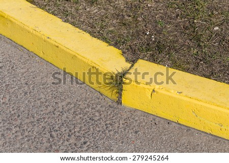 Yellow curb stone border and asphalt road - stock photo
