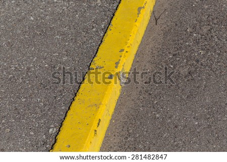 Yellow curb stone border and asphalt road