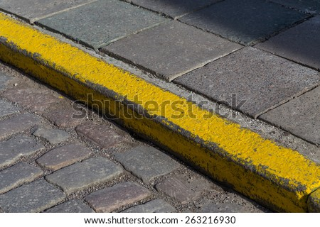 Yellow curb stone border in an old town road - stock photo