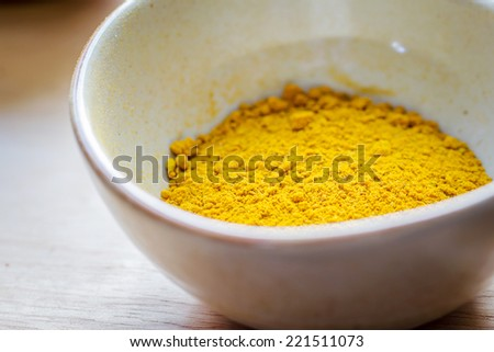 Yellow curry powder in  ceramic bowl on wooden table