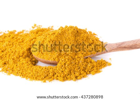 Yellow curry powder in the wooden spoon, isolated on white background.