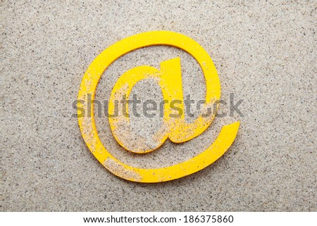 Yellow 3d email symbol in the sand - stock photo