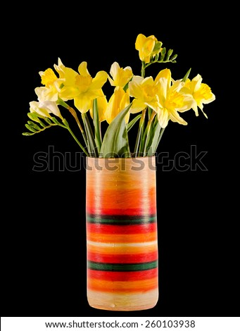 Yellow daffodils and freesias flowers in a vivid colored vase, close up, isolated, black background. - stock photo