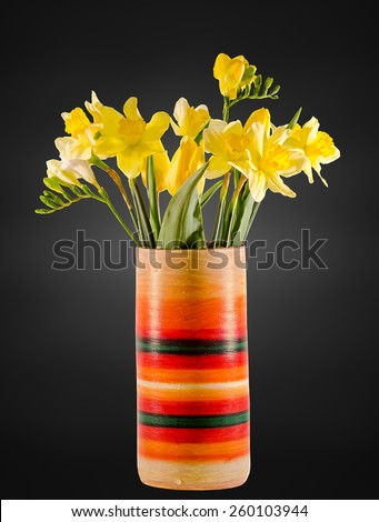 Yellow daffodils and freesias flowers in a vivid colored vase, close up, isolated, dark background. - stock photo