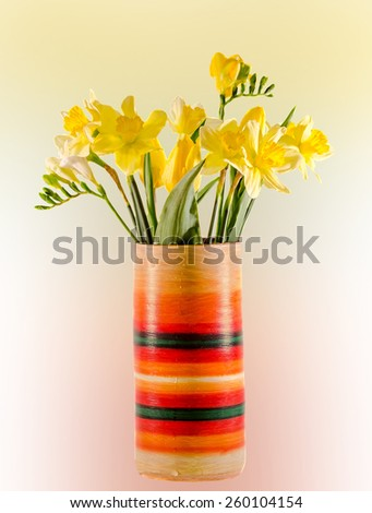Yellow daffodils and freesias flowers in a vivid colored vase, close up, isolated, degradee background. - stock photo