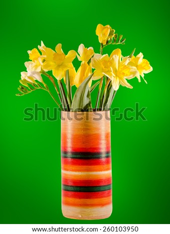 Yellow daffodils and freesias flowers in a vivid colored vase, close up, isolated, green background. - stock photo
