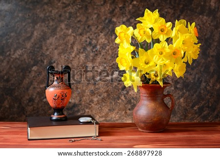 Yellow daffodils in a ceramic vase, amphorae and books - stock photo