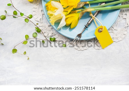 Yellow daffodils on blue plate with fork and table sign, spring decoration, top view, frame