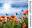 yellow daisy with butterflies against a blue sky - stock photo