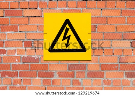 Yellow Danger of Death Warning sign on a brick wall - stock photo