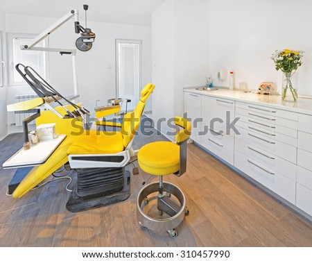 Yellow Dental Chair and Stool in Dentist Office - stock photo