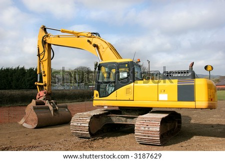 Yellow digger standing idle on a building construction site with an electricity sub station to the rear. - stock photo