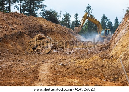 Yellow digger working on a road construction in mountain - stock photo