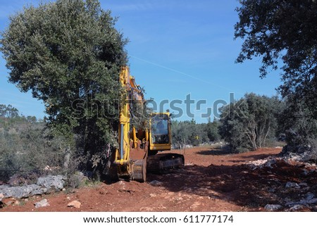 Yellow digger working on a road construction in mountain