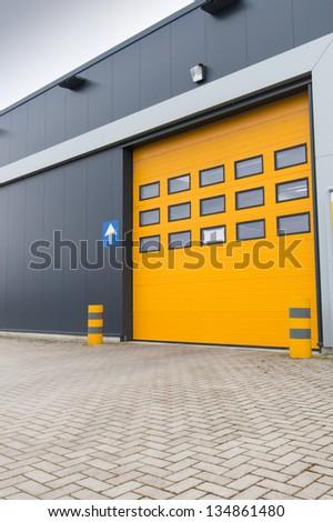 yellow door in storage building for recieving freight - stock photo