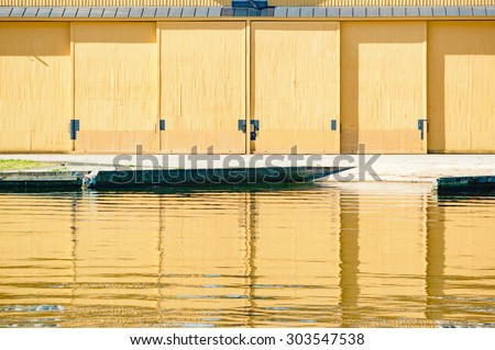 Yellow doors on a hangar are reflected in the calm water in front. Concrete ramp leads up to building from water. Hangar is closed. - stock photo