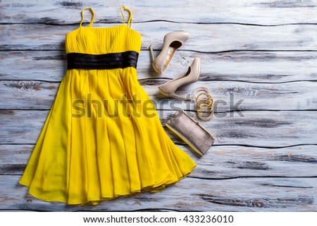 Yellow dress, purse and shoes. Casual yellow dress with accessories. Lady's charming summer outfit. New clothes and heel shoes. - stock photo