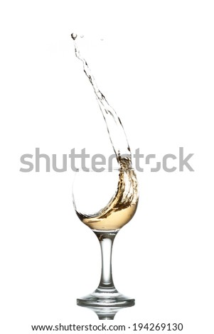 yellow drink splashes out of glass on white background