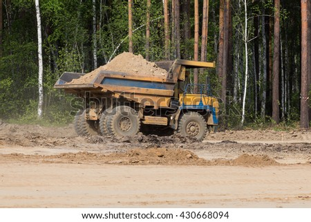 yellow dump truck transporting sand