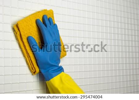 yellow duster to clean with a hand in blue with yellow glove on the white cells