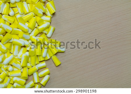 Yellow ear plug on the wooden background. - stock photo