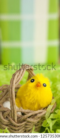 Yellow Easter fluffy chicken in wicker basket with egg on green background. Vertical image. Copy space. Shallow depth of field.