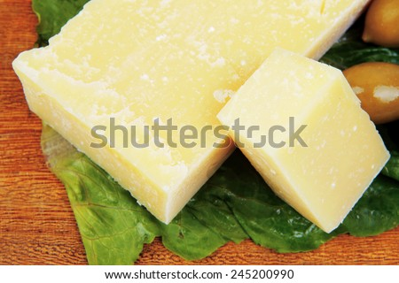 yellow edam cheese on wooden platter with olives and tomato isolated over white background - stock photo