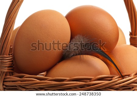 Yellow eggs in the wicker basket isolated on white background - stock photo