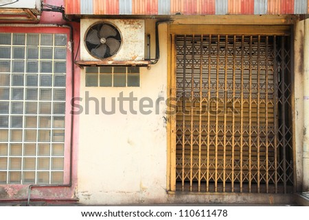 Yellow Elastic rusty metal gate and colorful awning at the wall - stock photo
