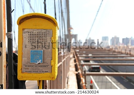 Yellow emergency call box on Brooklyn Bridge - stock photo