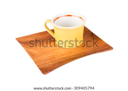 Yellow empty cup on a wooden plate isolated on white background - stock photo