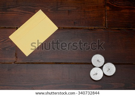 Yellow envelope and three candles on the wooden table - stock photo