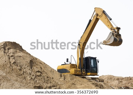 Yellow excavator and the sand on white background - stock photo