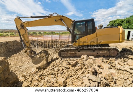 Yellow excavator digger on a building site digs through heavy stones to create a space for the cellar and foundations of a house construction.