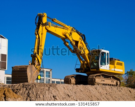 yellow excavator digging earth on construction site