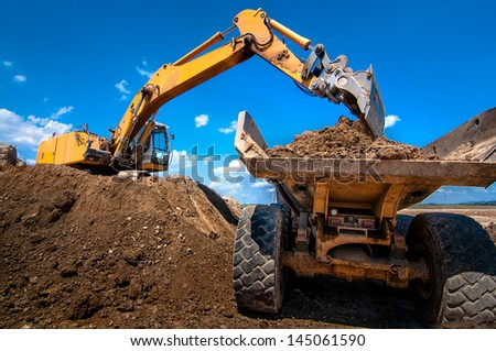 Yellow excavator loading soil  into a dumper truck on construction site - stock photo