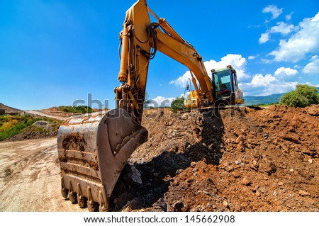 Yellow excavator moving soil and sand  on road construction site - stock photo