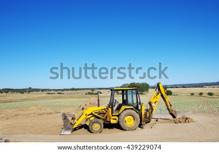 Yellow excavator on agriculture field - stock photo