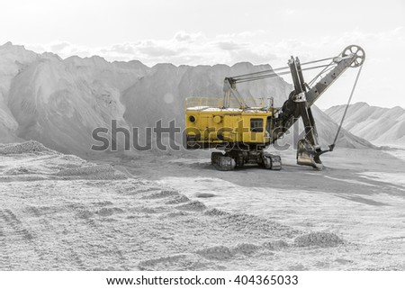 Yellow excavator standing among the rubble mountains in the black-and-white background