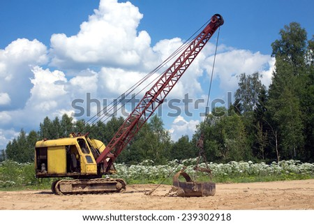 Yellow excavator with big heavy bucket standing on sand on background of forest and clear blue sky on a summer day - stock photo