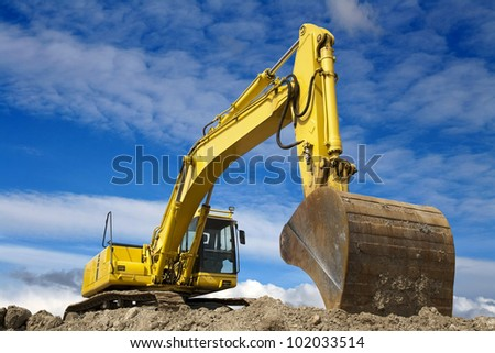 yellow excavator work in blue sky - stock photo
