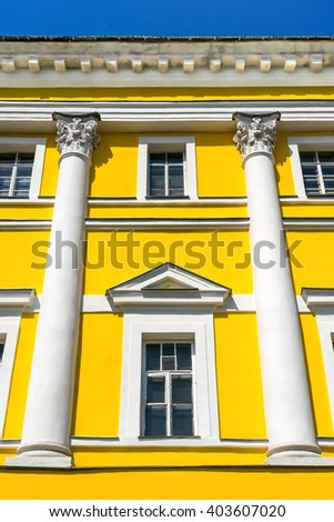 Yellow facade of a historic building with columns and windows, on the background of blue sky, an example of classical architecture - stock photo