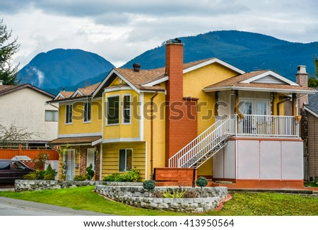 Yellow family house with mounting view on cloudy sky background. - stock photo