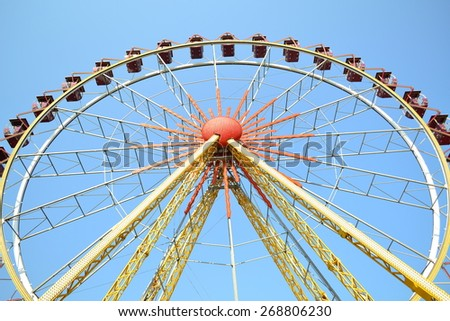 Yellow ferris wheel on a background of blue sky - stock photo