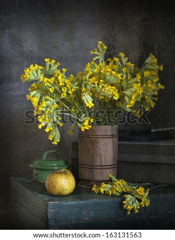 Yellow field flowers in a vase on a  wooden box