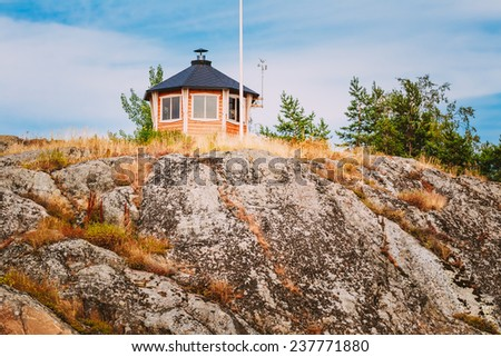 Yellow Finnish Lookout Wooden House On Rock In Island In Summer - stock photo