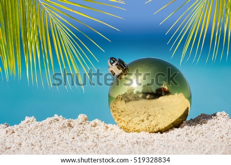 Yellow fir tree decoration ball on sandy beach, Tropical christmas and New Year celebration