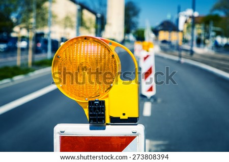 Yellow flashing light standing at road construction site. Road works concept. - stock photo