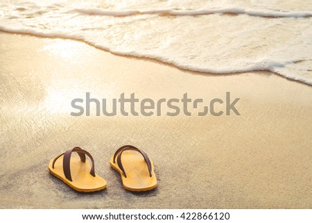 Yellow flip flop on the beach with bright light of sunset in summer - stock photo