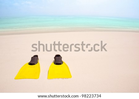 Yellow flippers on the sandy beach - stock photo